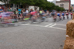 Motion Blur Of Cyclists Speeding Through Turn In Amateur Race. Athens, GA, USA - April 25, 2015: Motion blur of group of male cyclists turning a corner in an stock photo