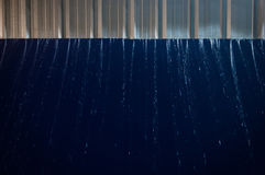 Motion blur of falling rain through the roof with blue sky. Royalty Free Stock Image