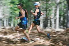 Motion blur forest trail run. Couple running fast through the forest on trail run with motion blur Royalty Free Stock Images
