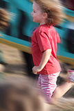 Motion blur girl in a race. Blurred motion shot of a young girl in a sports race stock photos