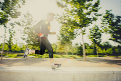 Motion blur image of young man running practicing sport in city park with extreme backlight lens flare Stock Photos