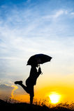 Motion blur jumping Umbrella girl with sunset Stock Photo