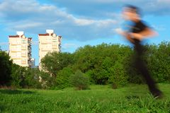 Motion blur man running in park and buildings Royalty Free Stock Photos