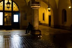 Motion blur of man smoking next to the columns at sukiennice Cloth Hall at night, with lamp lighting overhead. Krakow, Poland.  Stock Images
