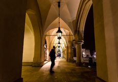Motion blur of man walking through the columns at sukiennice Cloth Hall at night, with lamp lighting overhead. Krakow, Poland. Motion blur of man walking Stock Photography