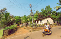 Motion blur from motorbike with tourists driving on village in popular Goa state, India. Rural landscape. Stock Image