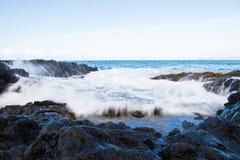 Motion blur of ocean waves crashing on rocks. Ocean waves crashing over lava rock stock photography