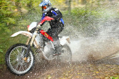 Motion blur, offroad motorbike crossing river Royalty Free Stock Images