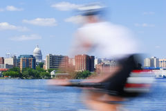 Motion blur of a person riding a bicycle past the capitol of Wis royalty free stock photography