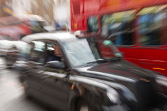Motion blur picture of Black Cab and Red Double Decker Bus in th Stock Photography