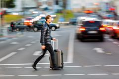 Businessman with trolley bag crosses the street. Motion blur picture of a businessman with trolley bag who crosses the street Royalty Free Stock Photo