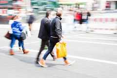 Shopping people crossing the street. Motion blur picture of shopping people crossing the street Royalty Free Stock Image