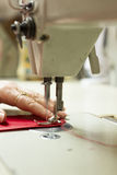 Motion Blur of Sewing Machine Needle Stitching Cloth. Motion blur of sewing machine needle stitching red cloth with tailor's hand as assist Stock Image