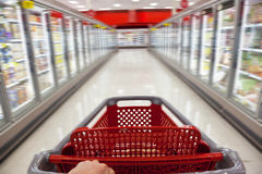 Motion Blur Shopping Trolley in Supermarket. A fast food concept motion blur shot of a shopping trolley being pushed down the aisle of a supermarket Stock Photo