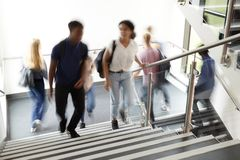 Motion Blur Shot Of High School Students Walking On Stairs Between Lessons In Busy College Building royalty free stock photography