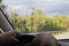 Motion blur. View of the forest road from the front window of the car. The driver`s hands, holding the steering wheel, in focus stock image