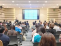 Motion blur of view of seminar with audience in a seminar room b. Motion blur of view of seminar with audience in seminar room background Stock Photos