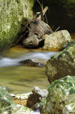 Motion blur water through rocks Stock Photos