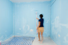 Motion blur woman painting wall in blue. Royalty Free Stock Image