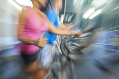 Motion Blur Zoom Man & Woman Using Gym Equipment. Motion blur zoom photograph of an interracial group of men and woman, running on equipment at a gym Royalty Free Stock Photo