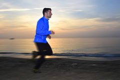 Motion blurred action of young sport man running outdoors on beach at sunset Royalty Free Stock Photography