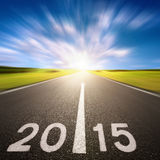 Motion blurred asphalt road forward to 2015 Stock Photography