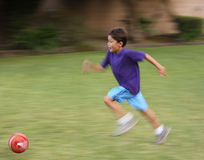 Motion blurred boy with soccer ball stock photo