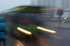 Motion blurred bus at dusk in inclement weather. On the street royalty free stock images