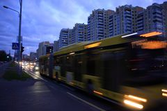 A blurred bus on the avenue at dusk. The motion of a blurred bus on the street at dusk royalty free stock photos