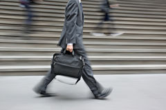 Motion blurred business people walking on the street Stock Photo