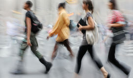 Motion blurred business people walking on the street Stock Images