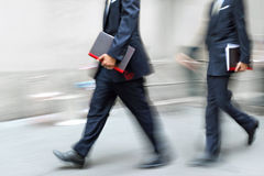 Motion blurred business people walking on the street Royalty Free Stock Photos