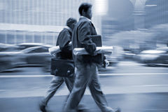 Motion blurred business people walking on the street Royalty Free Stock Image