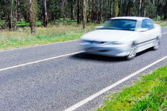 Motion blurred car driving along a quiet country road. Stock Photos