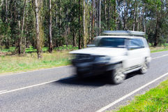 Motion blurred car driving along a quiet country road. Royalty Free Stock Photos