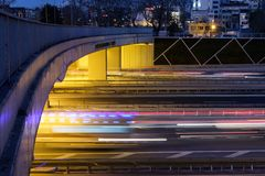 Motion blurred car lights coming out under a bridge at night stock photos