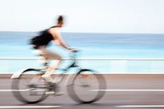 Motion blurred cyclist going fast on a city bike lane Royalty Free Stock Photos