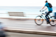 Motion blurred cyclist going fast on a city bike lane Royalty Free Stock Images