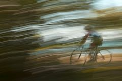 Blurred cyclist on lakeshore path. Motion blurred cyclist speeding along a city park bicycle path Royalty Free Stock Photos