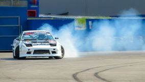 Motion blurred of driving a drift car by a skilled driver and having experience on a speed track. Abstract blurred drift car with smoke from burned tire royalty free stock photo