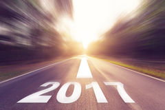 Motion blurred empty asphalt road and New year 2017 concept royalty free stock image