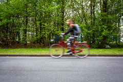 Motion blurred female biker on a city street, Stock Photography