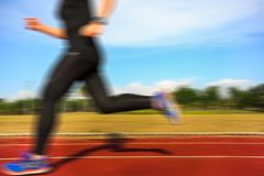 Motion blurred of female runner. On running track Royalty Free Stock Photos