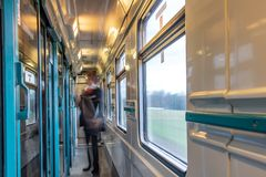 Motion blurred figure of conductor in the wagon. Of express train. The interior of moving train with long corridor and doors and windows stock images