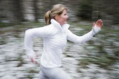 Motion blurred woman running outdoors in winter. Motion blurred fit woman running outdoors in winter Royalty Free Stock Photo
