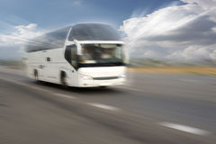 Motion blurred image of driving bus. Motion blurred white bus on the highway on a background of the sun`s rays through the clouds Stock Photography