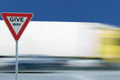 Motion blurred moving truck background, triangular give way text yield traffic sign. Motion blurred moving truck background triangular give way text yield royalty free stock photo