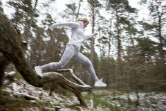 Motion blurred photo of woman exercising in forest in winter. Motion blurred photo of woman exercising in forest in cold weather Royalty Free Stock Photo