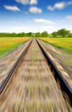 Motion blurred railway. Motion blurred railroad to horizon under blue sky Royalty Free Stock Photo