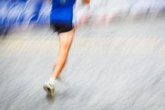 Motion blurred runner's feet in a city environment Royalty Free Stock Images